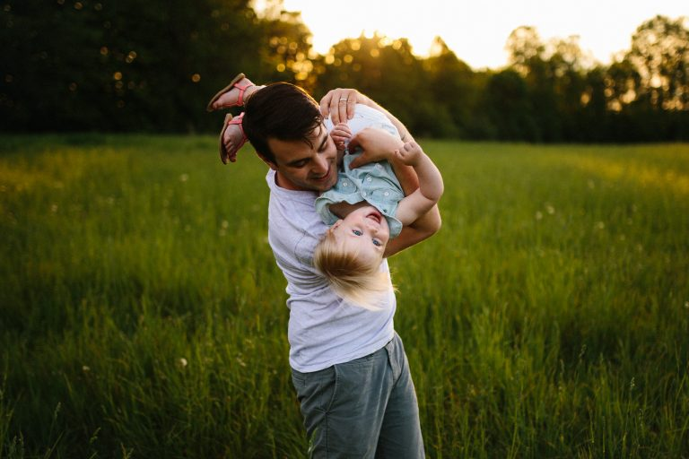 father and daughter having fun at sunset